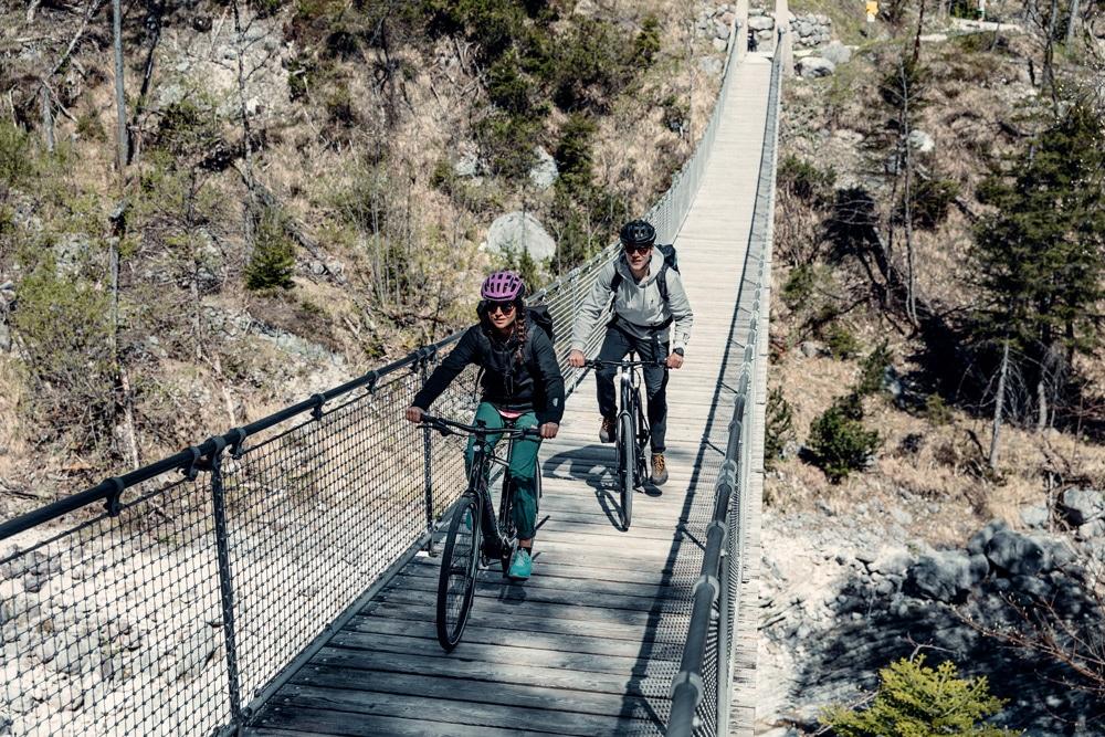 Eine Frau und ein Mann fahren mit ihrem Specialized e-Bike über eine Hängebrücke