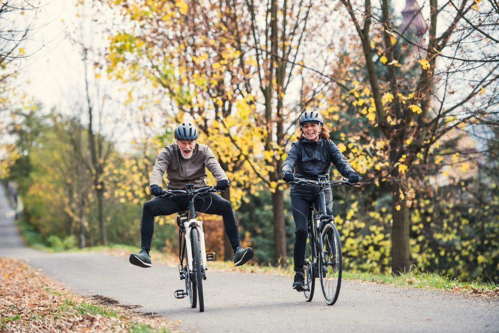 Ein aktives Seniorenpaar mit e-Bikes fahren draussen in der Natur