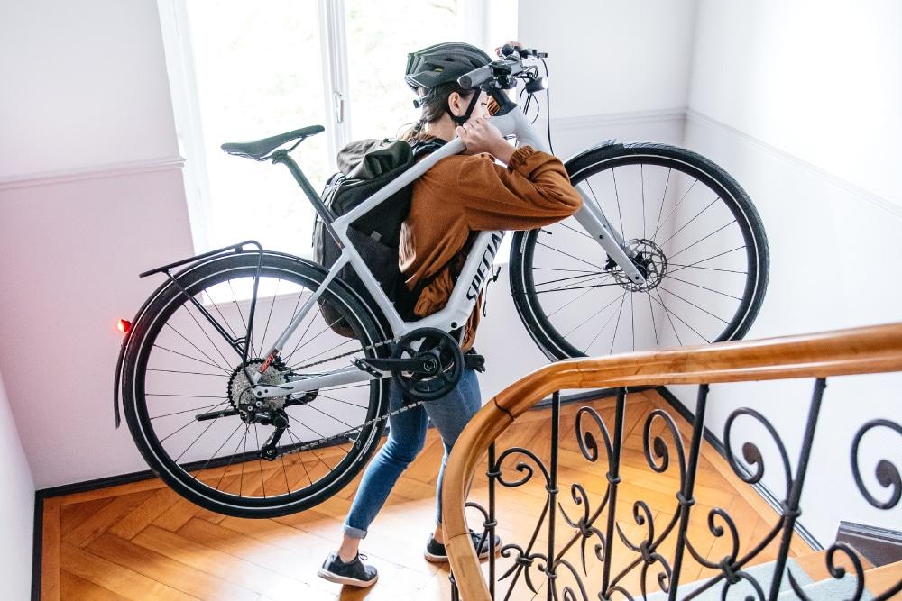 Eine Frau trägt ein Specialized Vado SL e-Bike in einem Treppenhaus die Stufen hinunter