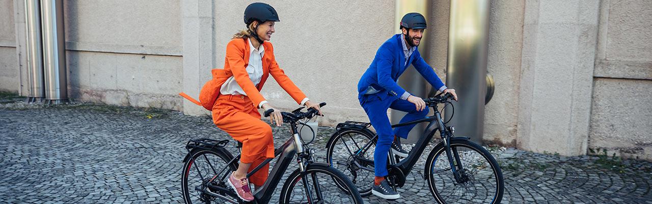 Ein Pärchen in Business-Kleidung auf dem Weg zur Arbeit auf zwei Hercules e-Bikes