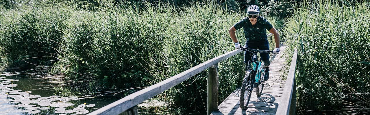 Ein Mann fährt mit einem Husqvarna e-Bike über einen Steg, der über einen See führt