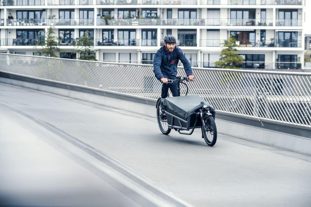 Mann fährt mit seinem Load 75 Lasten e-Bike von Riese & Müller durch die Stadt