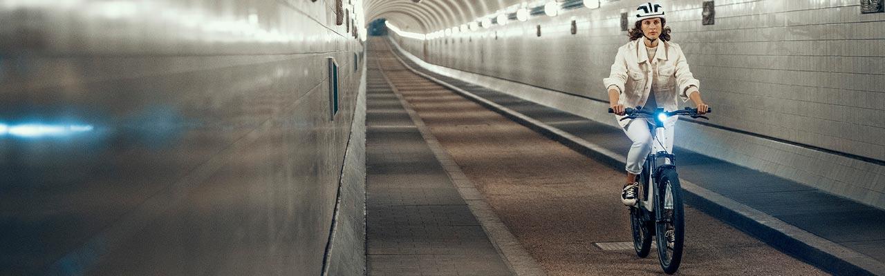 Eine Frau fährt auf einem Riese&Müller e-Bike durch einen Tunnel