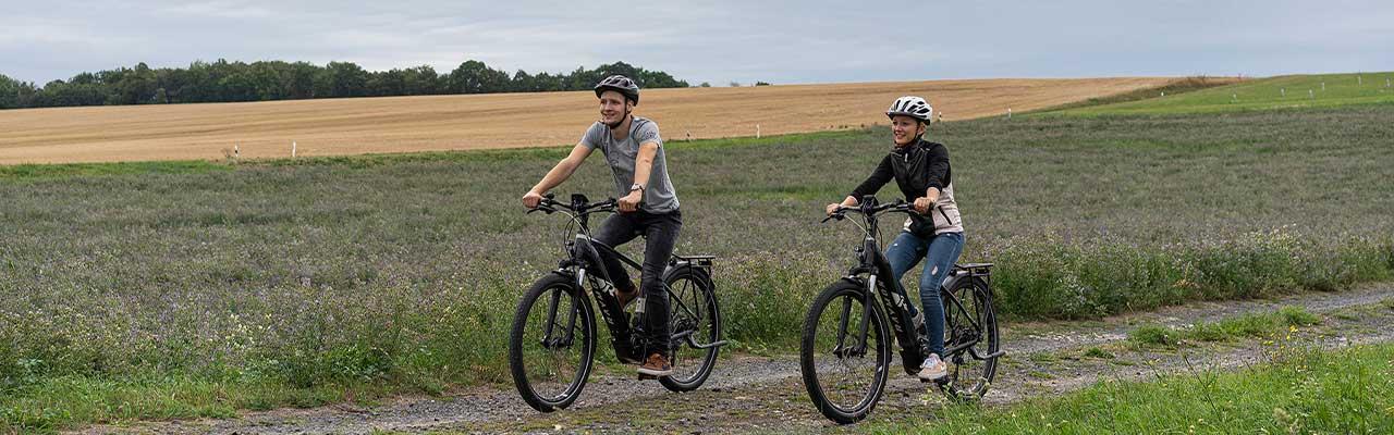 Zwei Personen fahren auf ihren R Raymon e-Bikes über einen Feldweg