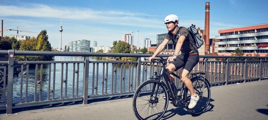 Mann fährt auf seinem e-Bike über Brücke in Berlin