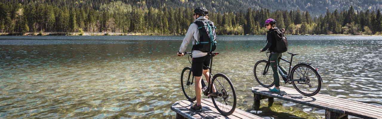 Zwei Personen fahren die Specialized Vado SL e-Bikes vor einer schönen Landschaft probe