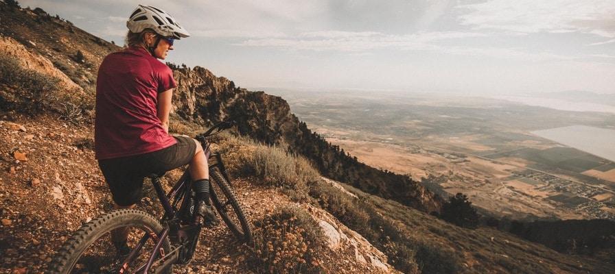 Frau geniesst den Ausblick vom Berg auf ihrem Specialized Levo