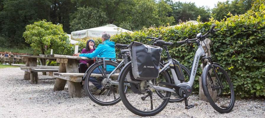 Zwei ältere Menschen sitzen draussen an einem Picknick-Tisch und davor parken zwei e-bikes.