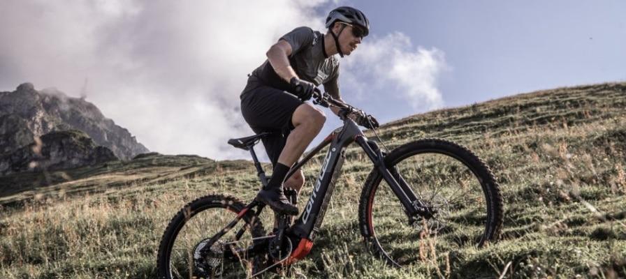 Mann mit e-Mountainbike am Hang eines Berges