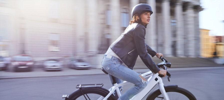 Frau fährt auf einem s-pedelec durch die Stadt.