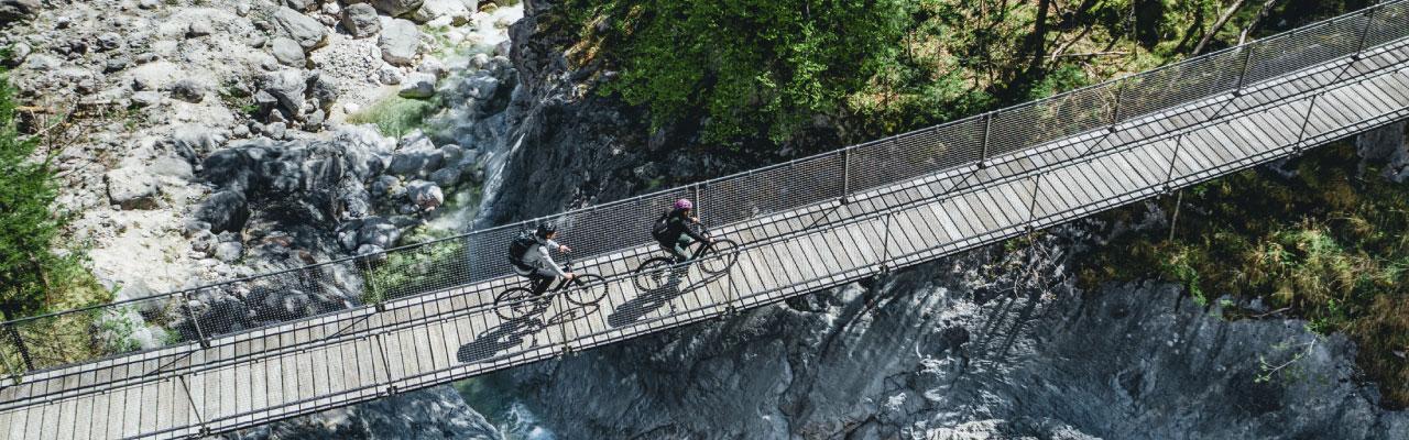 Zwei Personen fahren mit Specialized e-Bikes über eine Hängebrücke