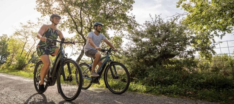 Mann und Frau fahren mit e-Bike auf asphaltierter Strasse durchs Grüne.