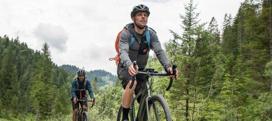 Zwei Männer auf e-Mountainbikes auf einem Schotterweg