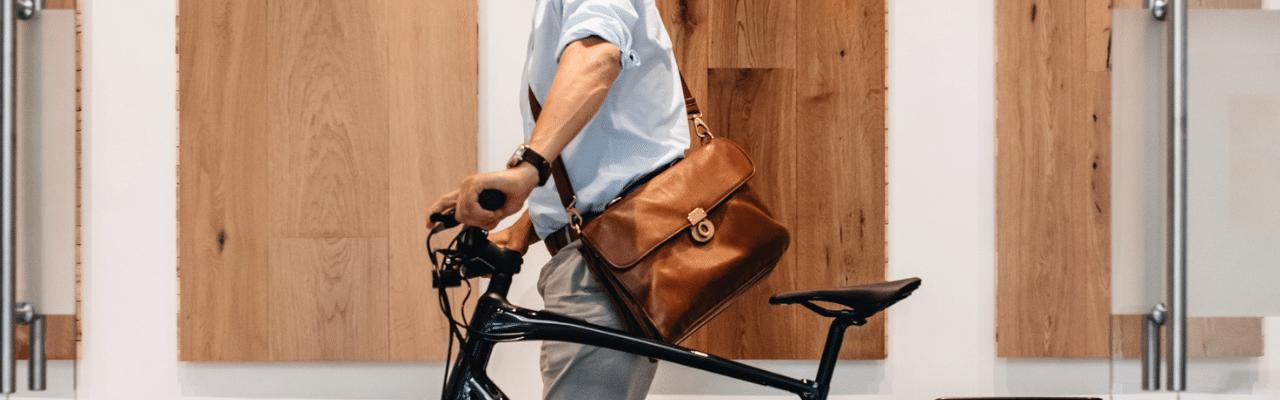 Mann schiebt sein e-Bike durchs Büro