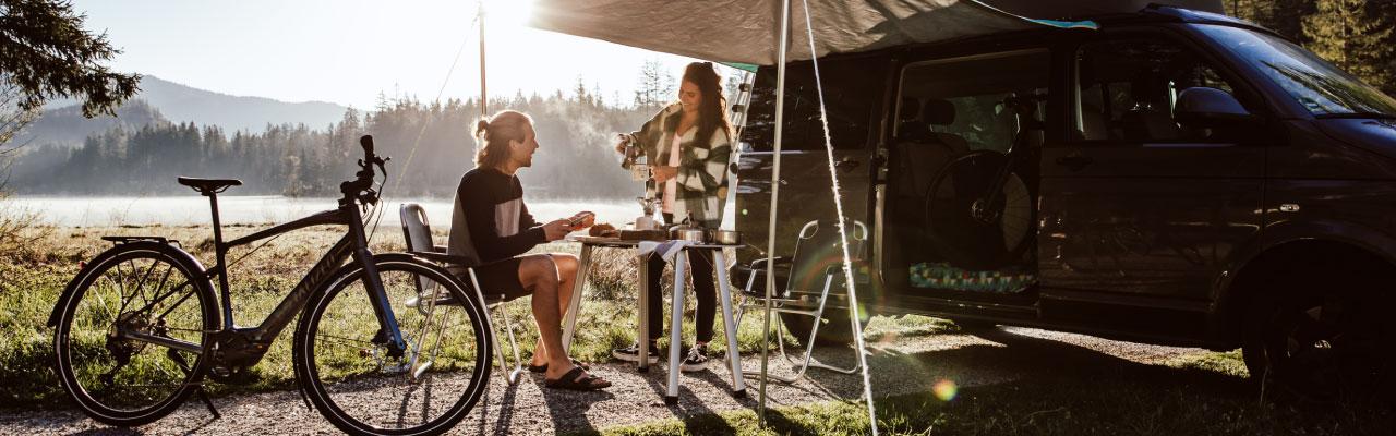 Ein Paar sitzt vor dem Campingwagen mit Specialized e-Bike
