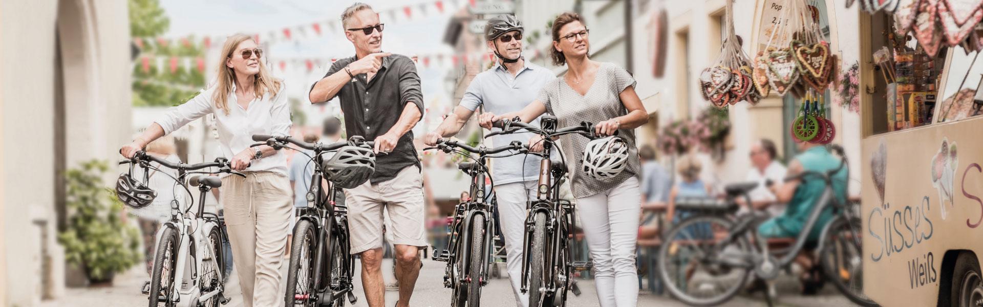 Vier Personen schieben ihre Winora e-Bikes durch die Innenstadt