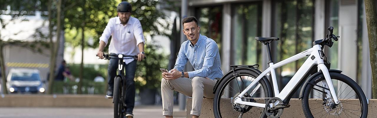 e-Bike Fahrer mit Handy sitzt neben weissem Stromer e-Bike