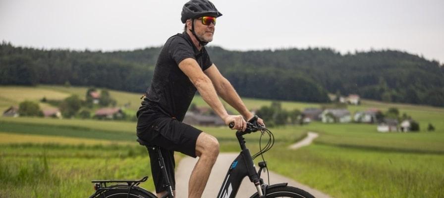Mann fährt auf KTM e-Bike in ländlicher Umgebung