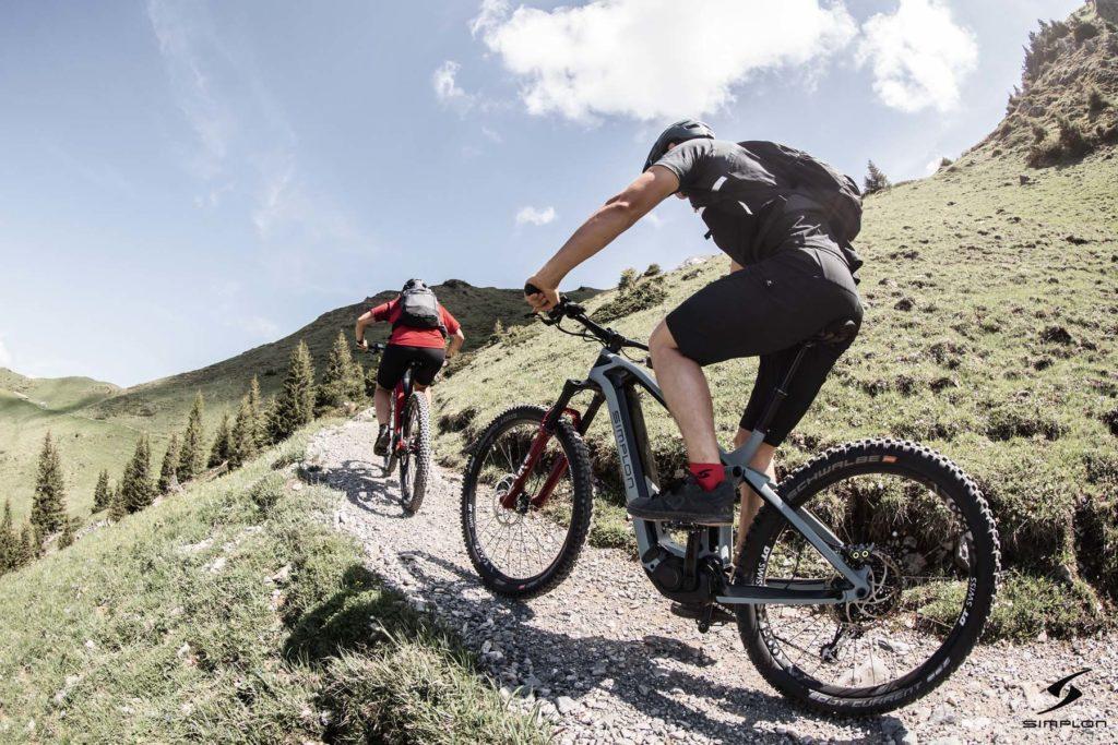 Zwei Biker fahren mit ihren e-MTBs von Simplon einen Berg rauf