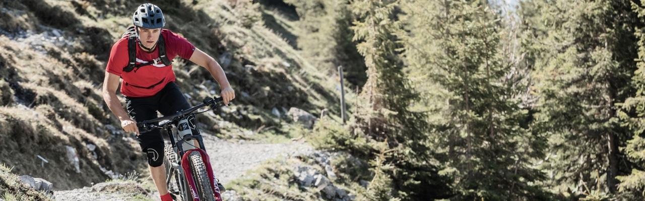 Mann fährt auf seinem Simplon e-Bike durch den Wald