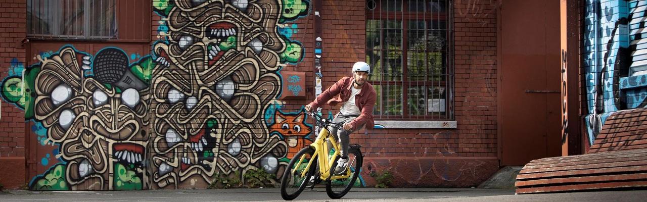 Mann fährt auf seinem sytlischen auffälligen Lifestyle e-Bike durch ein Szene Viertel