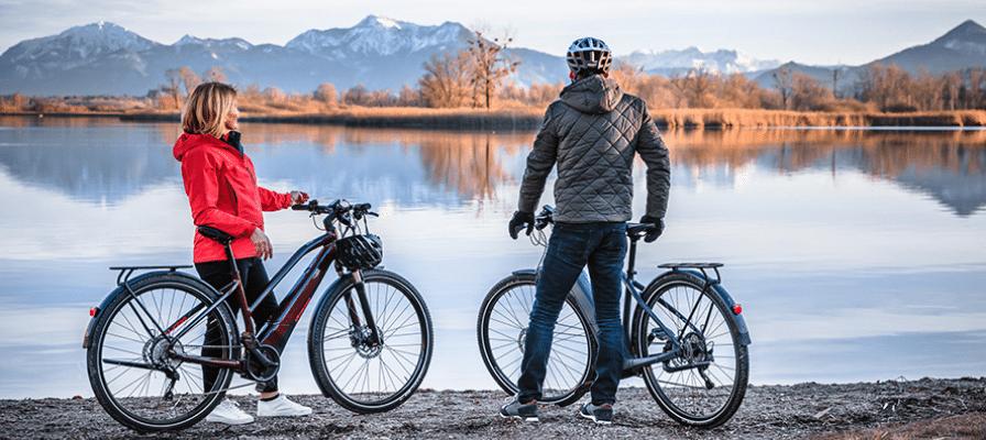 Ein Paar steht mit seinen Specialized e-Bikes vor einem See