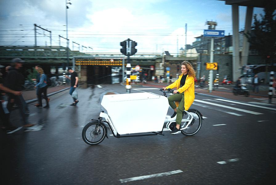 Eine Frau fährt mit ihrem Cargobike durch die Straßen