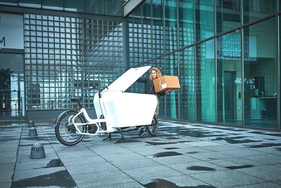 Eine Frau transportiert Kisten mit Hilfe eines Cargobikes