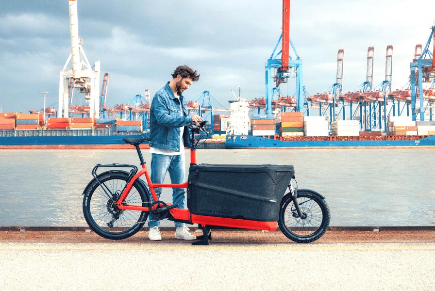 Ein Mann steht neben seinem Lastenfahrrad am Hafen